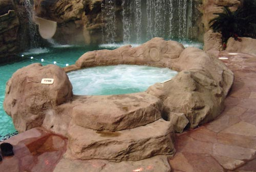 A hot tub sits just on the other side of the waterfall but blends in with the rock features surrounding it.