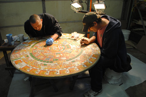 Two men work on the intricacies and detail work of staining and coloring the Aztec Calendar.