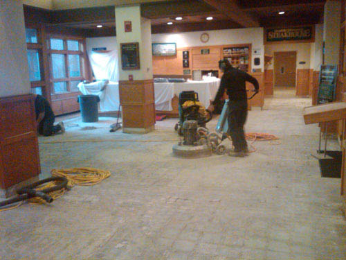 A man runs a grinding machine on a floor that removes the previously treated concrete.