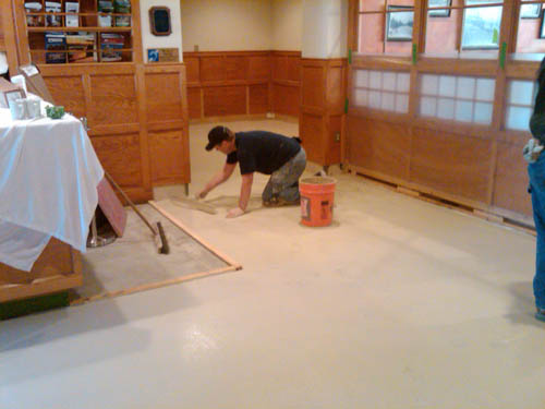 Placing the first coat of the trowelable overlay on the concrete floor.