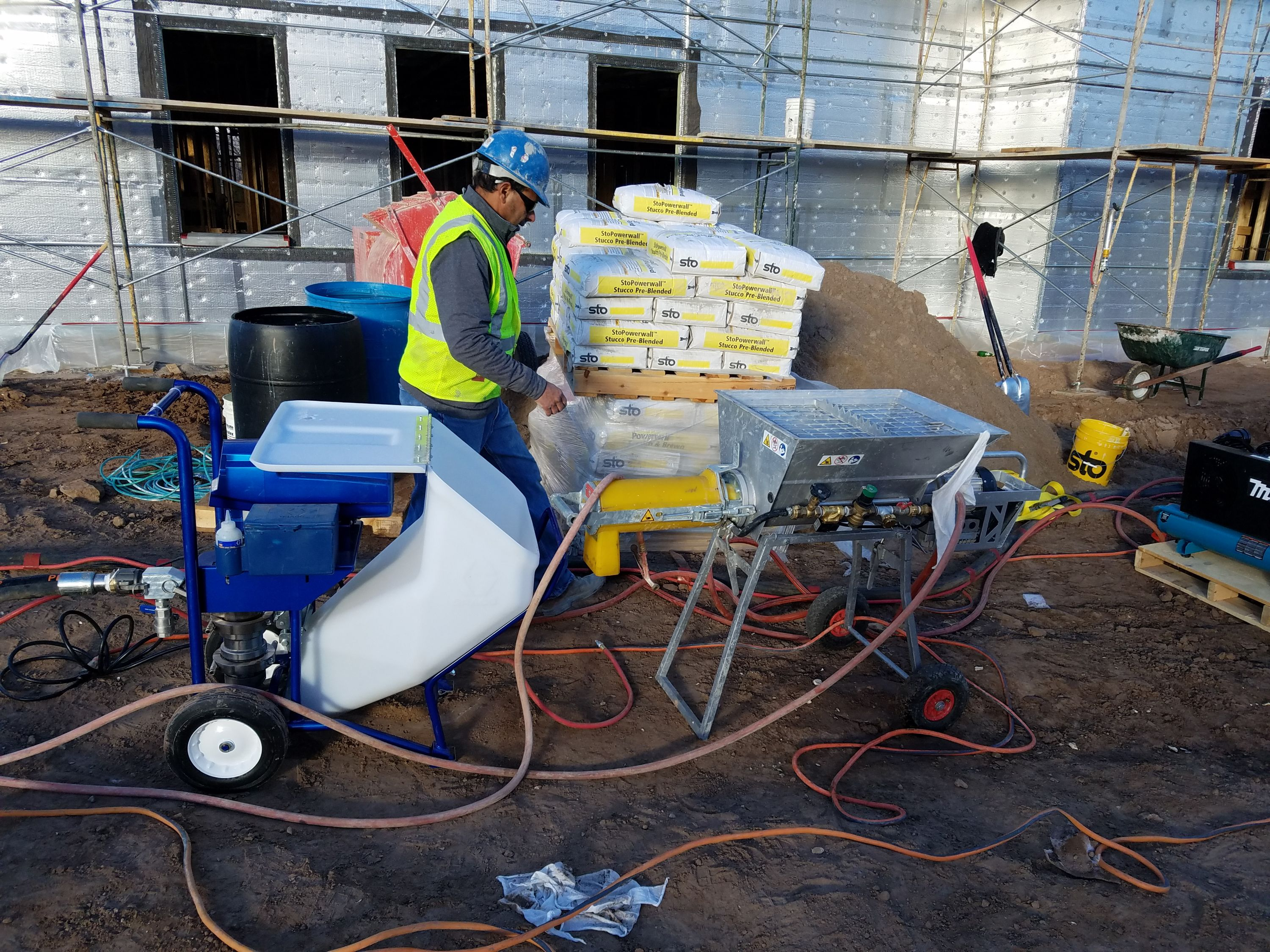 Danny Carillo preparing for applying concrete to the walls using a Graco Sprayer.