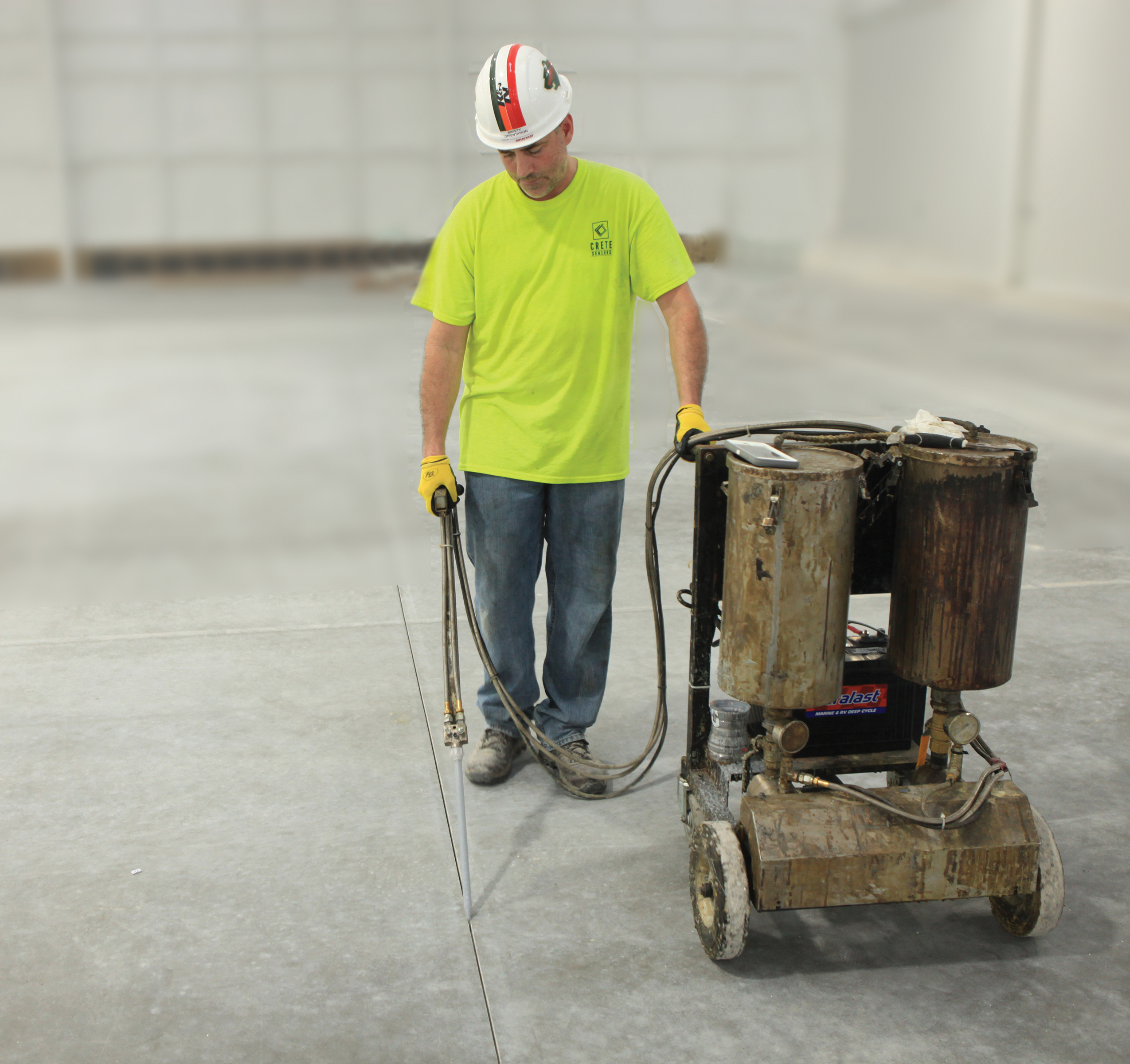 A man runs a machine that is created to fill concrete control joints.