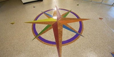 a brightly colored concrete compass rose in oranges, reds, purples and yellows achieved with Versatile Products.