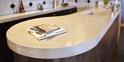 Round end to a sleek concrete countertop that has book stacked on it.
