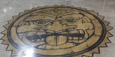 A sun king emblem on a concrete floor.