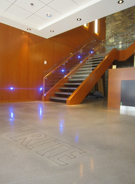 Modern stairs leading down to a concrete floor that has been engraved with the company name.