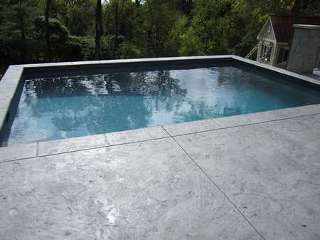 Gray concrete pool deck that is colored with darker undertones.