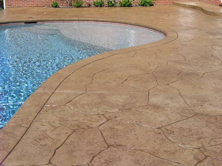 Stone look concrete that serves as a pool deck in a light tan color.