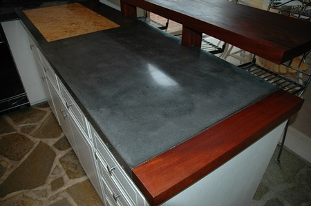 dark gray concrete countertop with a wood border.