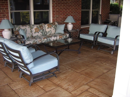Stamped concrete patio with blue cushioned lounge chairs.