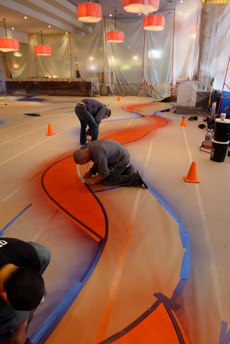 Workers placing color on a concrete floor.