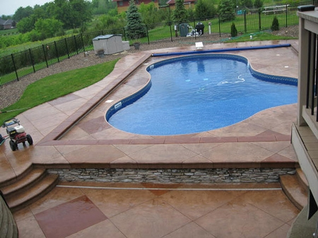 large outdoor swimming pool with a stamped and textured concrete deck