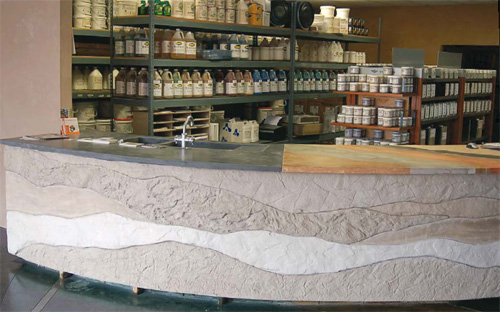 Concrete reception table in an art supply store shows of sediment layers of natural rock wall formations.