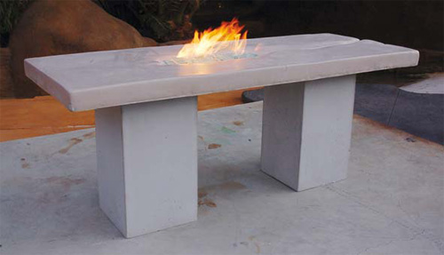 Concrete table with an integrated fire feature stands tall on large square concrete legs.