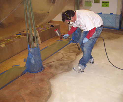 Trevor Foster of Miracote using an air paint sprayer to apply color to a concrete floor that has had a microtopping applied.