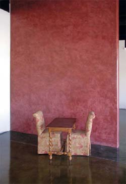 A red vertical concrete wall with two chairs and a table in front of it.