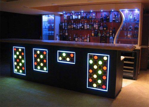 Installed in a residence, this bar includes personalized embeds and fiber optics in the top. It also features a curved concrete wall and concrete soffit to house the lighting. Also unique are the concrete panels with integrated squares and circles. Some of the circles are translucent embeds.