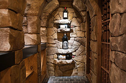 The cellar space starts out in the basement's hallway, with an elaborate glass and wrought iron door set in a beautiful faux-finished wall.