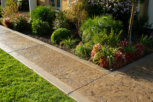 Neighborhood sidewalk featuring textured concrete with a smooth finished border.