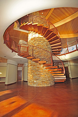 Tall spiral stair case surrounds a faux stone column above a stained concrete floor.