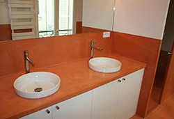 Orange concrete countertop in a bathroom with two white sinks.