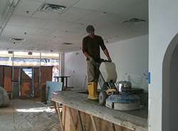 Custom Concrete Designs is standing on concrete countertop with a polishing machine. Grinding the top of a concrete countertop perfects the finish.