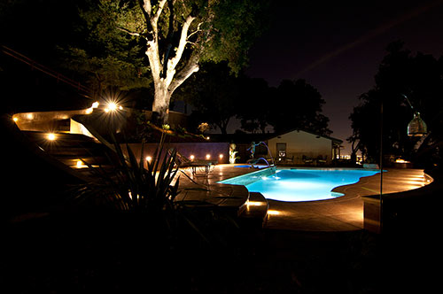 At night, this concrete pool deck is lit with well-placed lights and looks like a peaceful space.