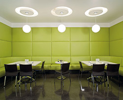 LIme green cushioned walls in a break room. Three round lights reflect circles on the ceiling above the black chairs and white tables.