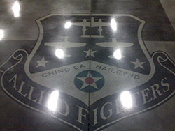 Allied Fighters logo within a polished concrete floors using dyes. Dyes are used in polished concrete not stains.