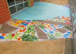Hand painted flora and fauna native to Texas as well as put down quotes that reflect their experiences with the youth arts organization all on a concrete overlay by Butterfield Color in Texas.