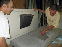 Two men inspecting the surface of a Self-consolidating concrete countertop vanity