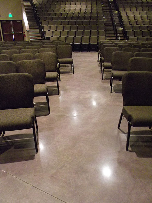 Chairs lined up in the worship space of this church atop polished concrete.