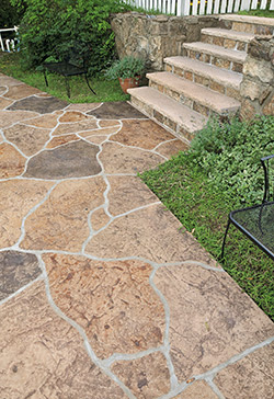 Natural stone look achieved with stamped concrete and neutral colored stains.