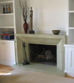 Concrete fireplace precast in a light gray green color has an architectural design element.