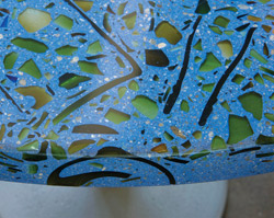 Recycle colored glass impregnated in a blue precast concrete countertop which was then ground to a smooth sheen.