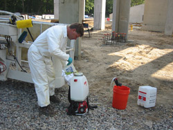 A Tom Ralston Concrete crew member fills up a gas-powered sprayer for acid staining.
