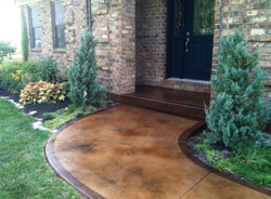 A stained concrete entryway in light brown with a dark brown border.