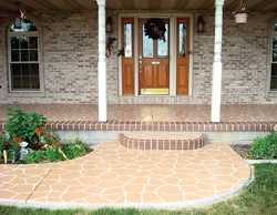 A stamped concrete entryway to a home with steps that are lined with brick-like stamp.