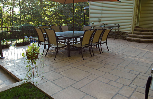 A stamped concrete patio with patio furniture.