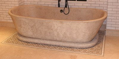 Sand colored concrete bathtub with subway tile surround sits away from the wall.