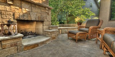Outdoor fireplace complete with patio furniture.