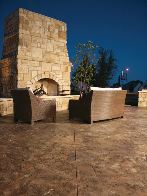 A look at a large concrete fireplace on an outdoor patio.