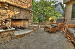 Patio furniture on a concrete patio in front of a large concrete fireplace.
