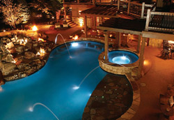 An aerial view of a pool lit at night with a reddish concrete pool deck.