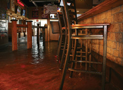 Brown stained concrete floor in a restaurant next to tall bar height chairs.
