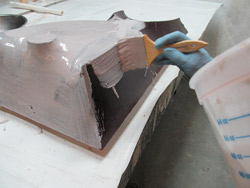 Forming concrete with fabric - After the first coats of resin are on and hardened, you can apply your Bondo-resin mix to get a sandable and workable surface.