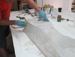 Forming concrete with fabric - Once all your coats are on, do a final sand to 120 grit. Then apply a layer of regular Bondo. This will allow you to fill in any low points or any possible wrinkling that may have occurred. When this coat hardens, you can sand to 120 again and work the surface into the final shape. Apply more Bondo if necessary to build up any area that is still too low or contains any imperfections.