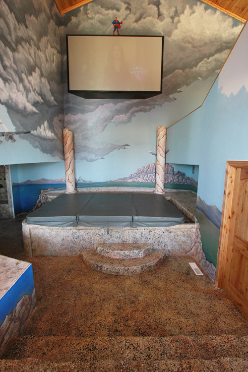 Superman painted on the wall above the hot tub in this man cave. Concrete steps lead into this space