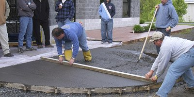 Screeding the concrete with a 2 x 4