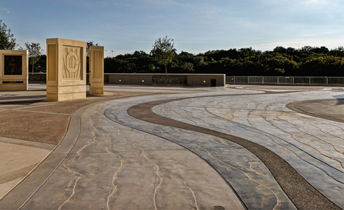 Texas Bomanite used a variety of finishes, stains and decorative saw cuts to highlight the work. The river itself consists of a band of seeded aggregate down the middle, flanked by stamped banks.